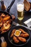 在黑色的盘子、油煎的土豆、啤酒和面包的鸡块 免版税库存照片
