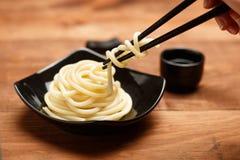 在黑色的盘子的意粉通心面有在木tabl的筷子的 库存图片