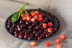 在黑色的盘子的新鲜的樱桃在自然亚麻制背景 免版税图库摄影