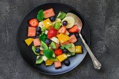 在黑色的盘子的新鲜水果沙拉 顶视图 免版税库存照片