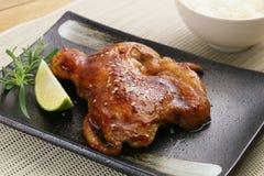 在黑色的盘子的烤鸡用切的柠檬和草本 图库摄影