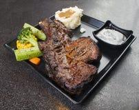 在黑色的盘子的烤黑安格斯牛排Ribeye 库存照片