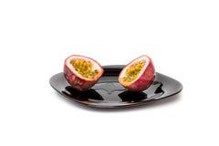 在黑色的盘子的被切的passionfruit 图库摄影