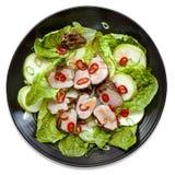在黑色的盘子被隔绝的顶视图的猪肉沙拉 免版税图库摄影