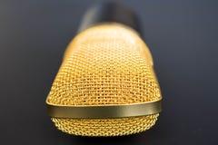 在黑色的金黄话筒 免版税库存图片