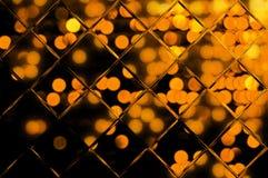 在黑色的金黄bokeh在玻璃后 免版税图库摄影