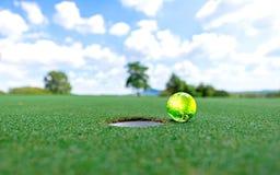 在绿色的绿土高尔夫球投入了蓝天背景 世界高尔夫球 免版税库存照片