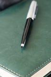 在绿色皮革笔记本关闭的黑金属笔 免版税库存图片