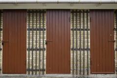 在黄色砖墙的三个红色木门 免版税库存照片