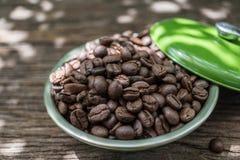 在绿色碗的咖啡豆在与阳光的老木背景 免版税库存照片