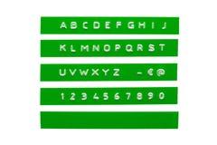 在绿色磁带上的压印的字母表 免版税库存照片