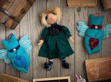 在绿色礼服的滑稽的手工制造玩偶在木桌上 免版税图库摄影