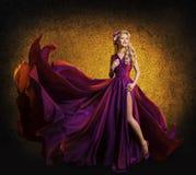 在紫色礼服,摆在飞行丝绸布料挥动的妇女的模型 免版税库存图片