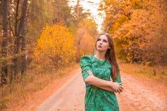 在黄色秋叶的美好的女孩模型 免版税库存照片