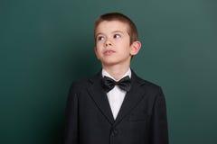 在绿色空白的黑板背景附近的男生画象,穿戴在经典黑衣服,一个学生,教育概念 库存图片