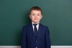 在绿色空白的黑板背景附近的男生画象,穿戴在经典黑衣服,一个学生,教育概念 免版税库存照片