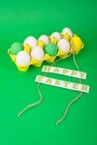 在黄色纸盒的五颜六色的复活节彩蛋 免版税库存图片