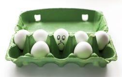 在绿色纸盒的哀伤的蛋面孔 免版税库存图片