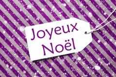 在紫色纸,雪花,茹瓦约Noel的标签意味圣诞快乐 免版税库存图片