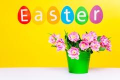 在绿色罐的桃红色花在桌,词复活节上 免版税库存图片
