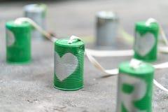 在绿色罐头的银色心脏连接用在水泥地板上的绳索 免版税库存照片