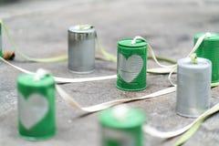 在绿色罐头的银色心脏连接用在水泥地板上的绳索 免版税库存图片