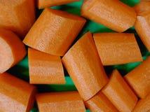 在绿色背景切开的新鲜的红萝卜大块 库存图片