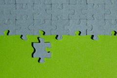 在绿色背景删去的一个七巧板片断 免版税库存图片