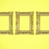 在黄色背景的三个金古色古香的照片框架 免版税库存照片