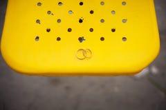 在黄色背景的两个婚戒 图库摄影