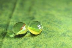 在绿色背景的两块大理石 免版税库存照片