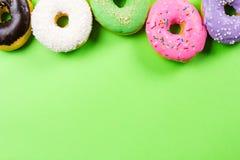 在绿色背景的五颜六色的圆的油炸圈饼 平的位置,顶视图 库存图片