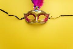 在黄色背景的五颜六色的狂欢节或carnivale面具 屏蔽威尼斯式 顶视图 库存照片