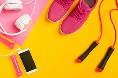 在黄色背景的健身辅助部件 运动鞋、哑铃,耳机和聪明 库存照片