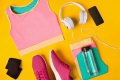 在黄色背景的健身辅助部件 运动鞋、瓶水,耳机和体育冠上 库存照片