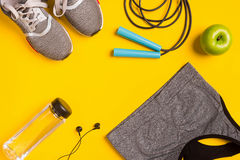 在黄色背景的健身辅助部件 运动鞋、瓶水,耳机和体育冠上 免版税库存照片