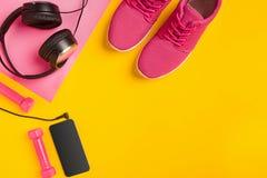 在黄色背景的健身辅助部件 运动鞋、瓶水,耳机和哑铃 库存照片