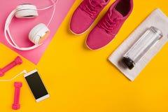 在黄色背景的健身辅助部件 运动鞋、瓶水,耳机和哑铃 库存图片