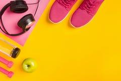 在黄色背景的健身辅助部件 运动鞋、瓶水,耳机和哑铃 免版税库存图片