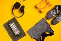 在黄色背景的健身辅助部件 运动鞋,瓶水,聪明,毛巾和体育冠上 库存照片