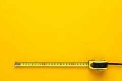 在黄色背景的卷尺 免版税图库摄影