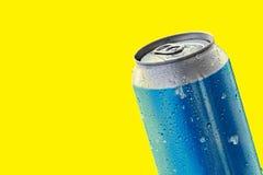 在黄色背景的发光的蓝色铝罐 免版税库存图片