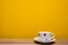 在黄色背景的咖啡杯 免版税库存图片