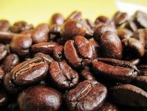 在黄色背景的咖啡豆 免版税图库摄影