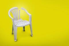 在黄色背景的塑料椅子 免版税库存图片