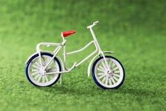 在绿色背景的小玩具自行车 库存图片