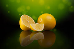 在绿色背景的柠檬与梯度和反射 免版税库存图片