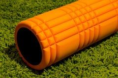 在绿色背景的橙色泡沫路辗 免版税库存图片