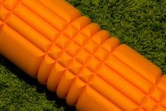 在绿色背景的橙色泡沫路辗 库存图片