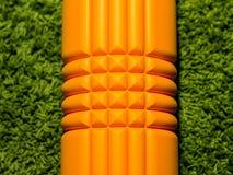 在绿色背景的橙色泡沫路辗 库存照片
